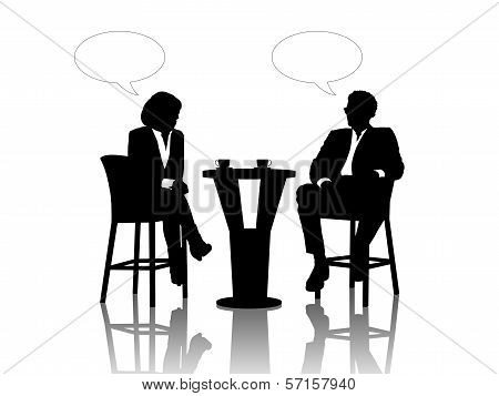 Businessman And Businesswoman Speaking At The Table Drinking Coffee
