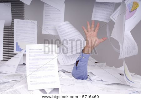 Business Man Drowning In A Desk Full Of Papers