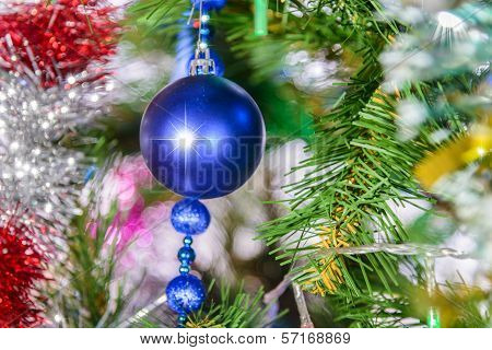 Christmas Decorations Hanging On A Pine Tree With Glitter,