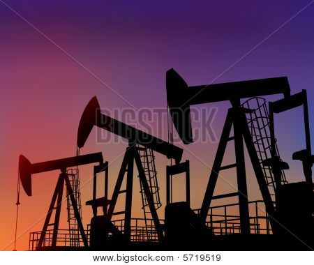 Three Oil Wells In The Desert At Dusk