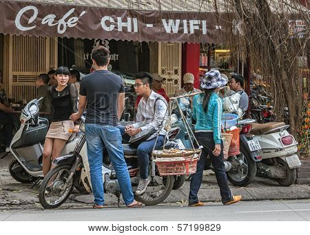 Street Scene With Young People Chatting And Food Vendor In Front Of Cafe.