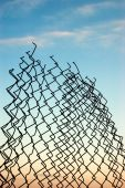 image of chain link fence  - Broken chain link fence against blue sky in the sunset - JPG