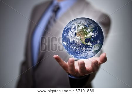Businessman holding the glowing world in his hands Earth image courtesy of Nasa at http://visibleearth.nasa.gov