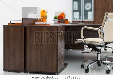 desk, leather armchair and bookcase on a white wall