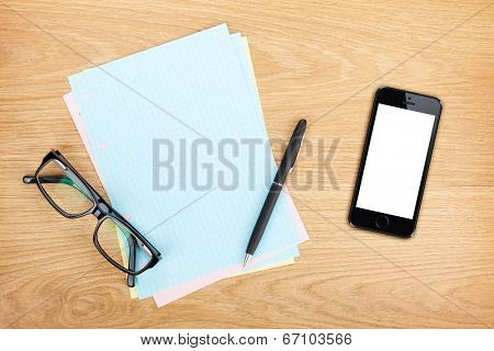 Blank lined paper with mobile phone, office supplies and glasses on wooden table. Above view