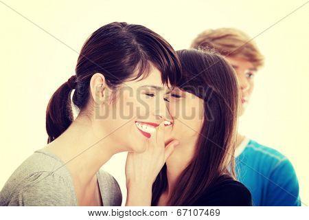 Two girls talking gossip about boy