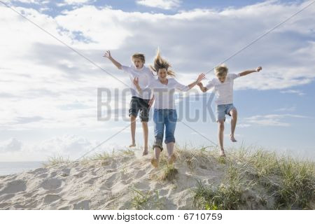 Mum And Sons Jumping Of A Sand Dune At The Beach