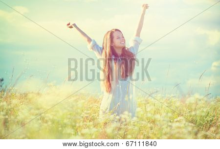 Beauty Girl Outdoors enjoying nature. Beautiful Teenage Model girl in white dress having fun on summer Field with blooming flowers, Sun Light. Glow Sun. Free Happy Woman. Toned in warm colors