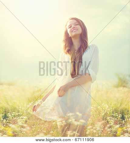 Beauty Summer Girl Outdoors enjoying nature. Beautiful Teenage Model girl in white dress on a Field with blooming wild flowers, Sun Light. Free Happy Woman. Toned in warm colors