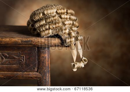 Antique barrister's wig lying on an old wooden desk