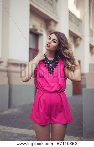 Fashion, Glamorous And Attractive Woman Dressed In A Sexy Sleeveless Pink Jumpsuit With A Hand In He