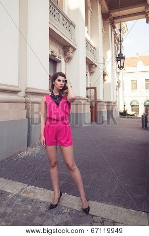 Fashion And Attractive Woman Dressed In A Sexy Sleeveless Pink Jumpsuit Posing In Full Body Length W