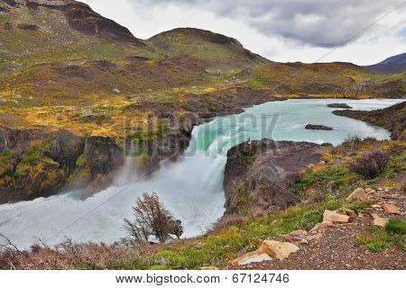 Affluent bustling Salto Grande waterfall with emerald water. On the edge of the cliff stands woman- tourist. Gorgeous National Park in Chilean Patagonia