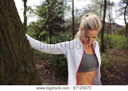 Beautiful Young Woman Resting After Jogging In A Park