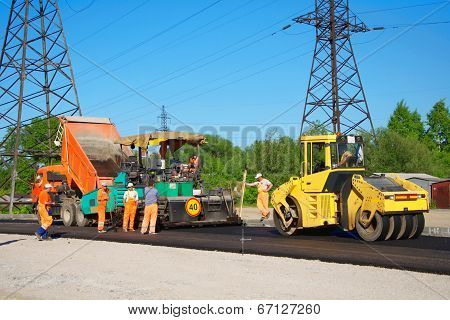 Road Paving With Truck, Rolling Machinery And Workers