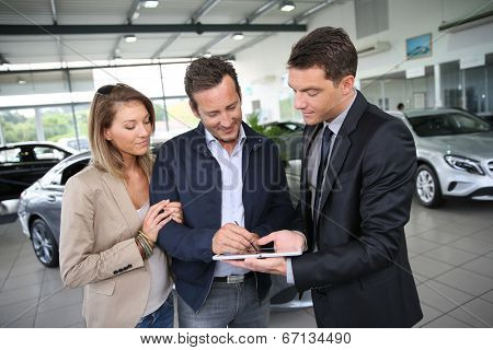 Couple signing car purchase order on digital tablet