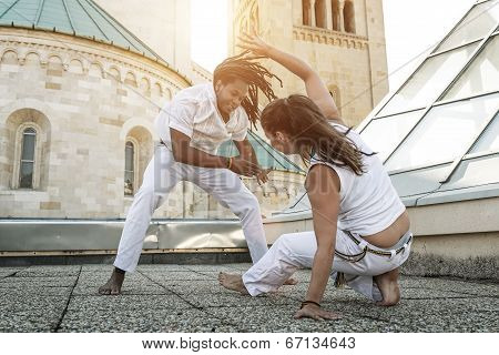 Young pair capoeira partners performing kicks outdoor