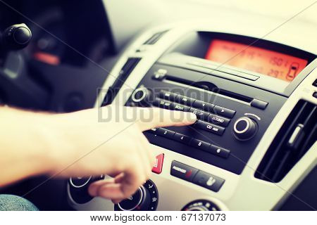 transportation and vehicle concept - man using car audio stereo system