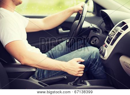 transportation and vehicle concept - man shifting the gear on car manual gearbox