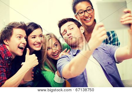 technology concept - group of students making picture with tablet pc