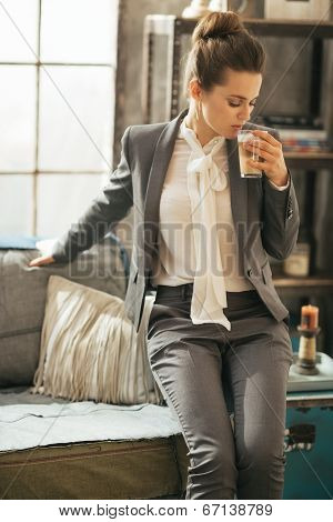 Business Woman With Coffee Latte Sitting On Divan In Loft Apartm