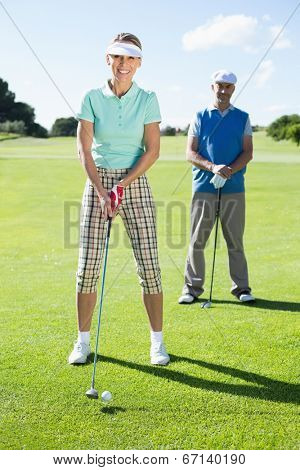 Smiling lady golfer teeing off for the day watched by partner on a sunny day at the golf course