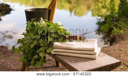 Finnish Summer Landscape And Sauna Objects On Bench By Lake.