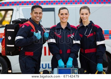 happy paramedics carrying portable equipments in front of ambulance