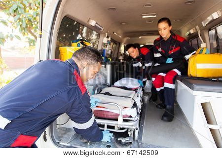 team paramedics taking stretcher out of an ambulance