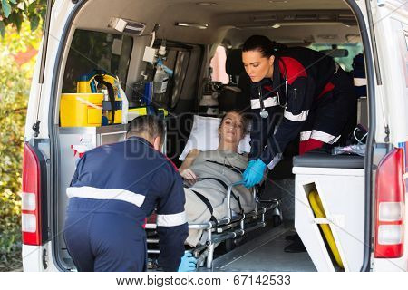 emergency medical staff team transporting patient to hospital with ambulance