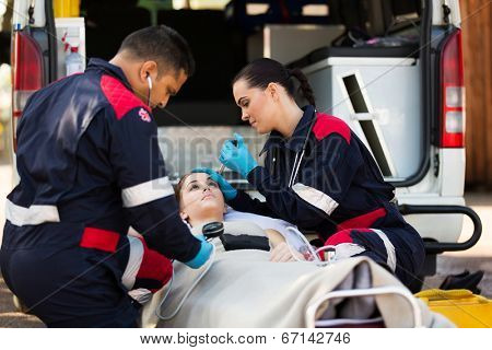 paramedic team examining young female patient