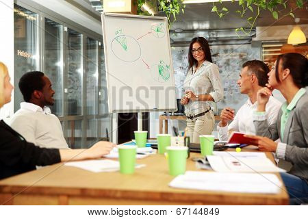 Young smiling businesswoman explaining graph to his colleagues