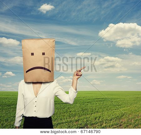 sad businesswoman pointing at something over green field