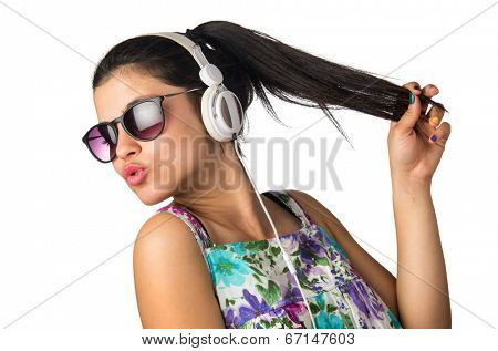 Pretty young girl with headphones and sunglasses dancing and holding her hair