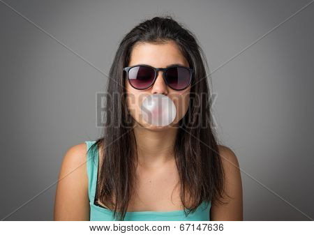 Brunette teenager girl with sunglasses blowing a bubble gum balloon