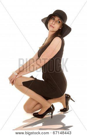 Woman Black Dress And Black Hat Kneel Look Back