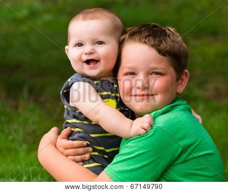 Happy Brothers Hugging In Summer Portrait Outdoors