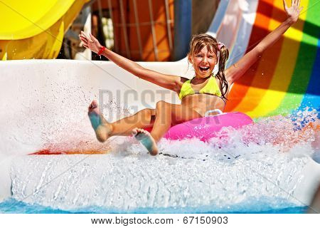 Happy child girl in yellow bikini sliding water park.