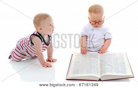 Little smart boy reads a big book.