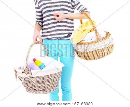 Woman holding laundry baskets with clean clothes, towels and pins, isolated on white