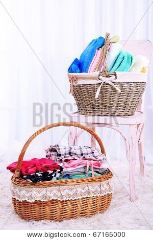 Colorful towels and clothes in baskets on table, on interior background