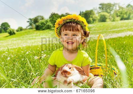 Smiling girl wearing flowers circlet and rabbit