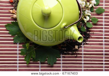 Herbal natural floral tea infusion with dry flowers and herbs ingredients, on bamboo mat background