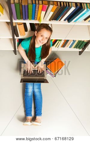 Smiling girl sitting on floor with laptop look up