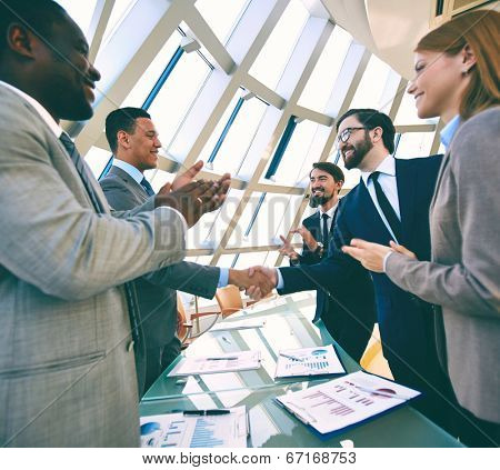 Group of business people clapping their hands while their colleagues handshaking