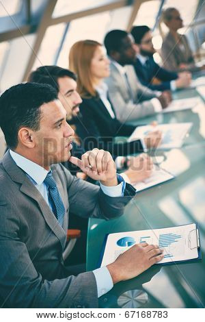 Pensive young businessman listening to explanations at seminar on background of other listeners
