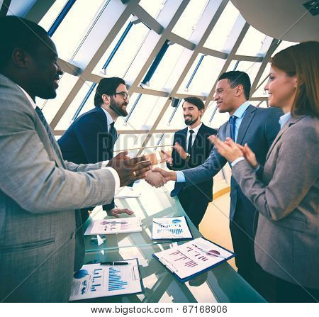 Group of business people congratulating their colleagues with promising deal