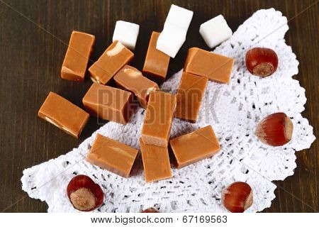 Many toffee on napkin on wooden table