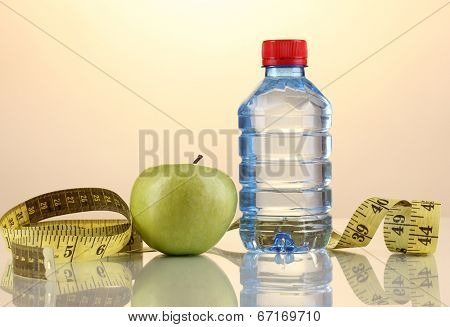 Bottle of water, apple and measuring tape on orange background