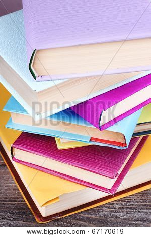 Stack of colorful hardback and paperback books, close-up